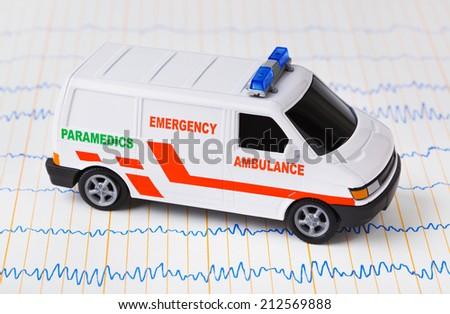 Toy ambulance car on ecg - medical background - stock photo