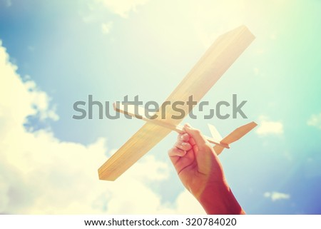 Toy balsa wood airplane in the sky. Toned filtered Instagram image - stock photo