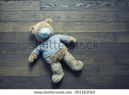 Toy bear in medical bandage lying on the floor - stock photo