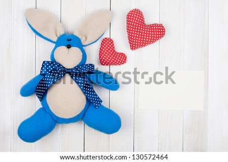 Toy bunny, love hearts, card on white wood background - stock photo