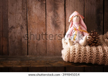 Toy bunny with woolen scarf on wooden background - stock photo