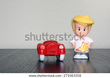 Toy car and boy figure - stock photo