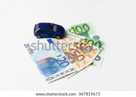 Toy car and fanned euro notes on white background