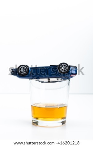 toy car and glass of whiskey metaphor crash accident isolated on white - stock photo