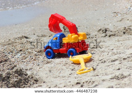 toy car excavator and scoop on the sandy coast. summer holiday by the sea - stock photo