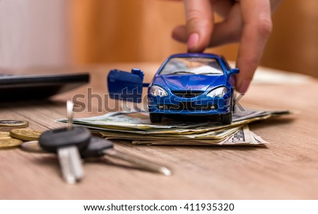 Toy car, keys and money on table - stock photo