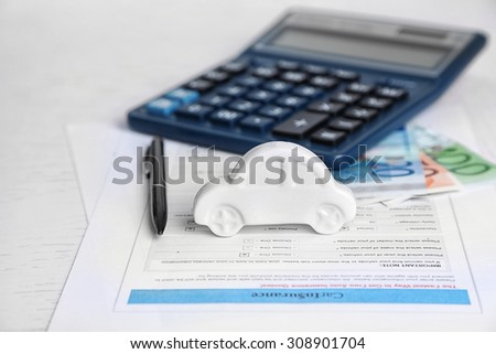 Toy car, money, documents and calculator on table. Car insurance concept - stock photo