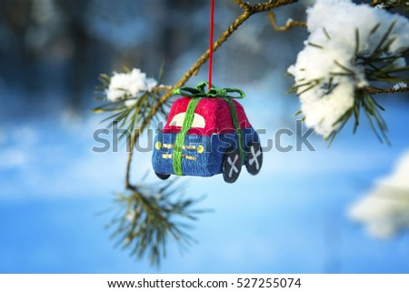 Toy car on a fir-tree branch in the snow-covered wood. Christmas background
