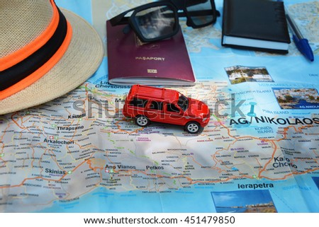 Toy car on a road map and traveling kit  - stock photo