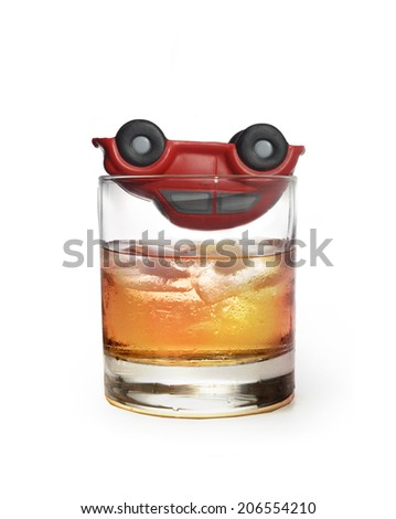 toy car up side down on top of glass of whiskey metaphor crash accident  isolated on white background representing safe driving and warning the danger of drinking alcohol and being a drunk driver - stock photo