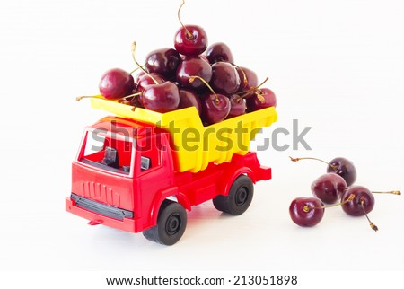 toy car with a sweet cherry in the white  background - stock photo