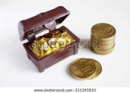 Toy chest full of gold coins and a pile of coins over white background. Toy chest and coins. - stock photo