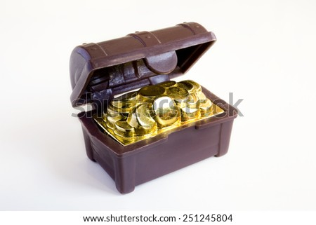Toy chest full of gold coins over white background. Toy chest. - stock photo