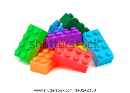 Toy colorful plastic blocks on white background - stock photo