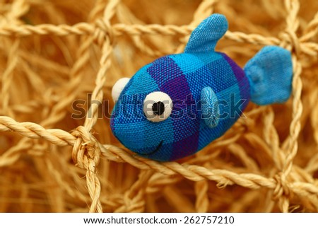 Toy cotton blue fish on the background of decorative fishing net, close up - stock photo