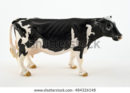 Toy cow isolated on a white background. Black and white spotted cow. Farm animals/Black and white spotted cow.