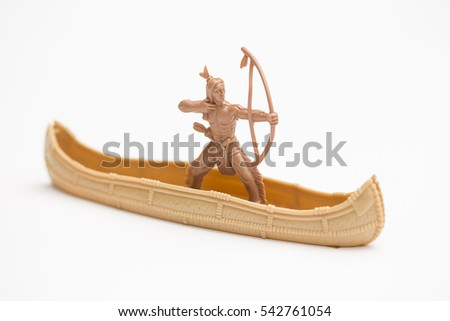 Toy cowboy with bow in a canoe