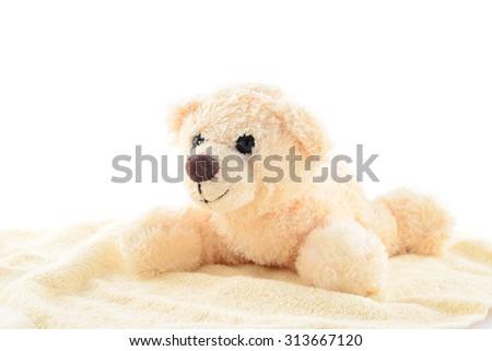 Toy cream teddy bear on cream cloth isolated on white background - stock photo