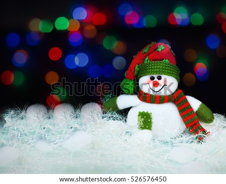 Toy decorated with a snowman, on a black background