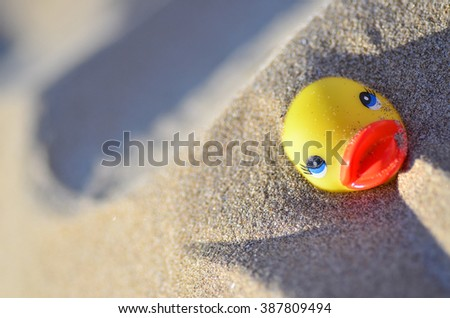 Toy duck on the beach in the sand - stock photo