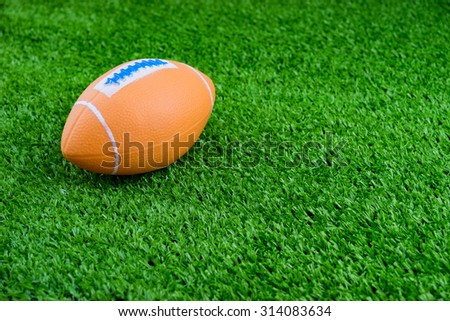 Toy football on artificial grass background - stock photo