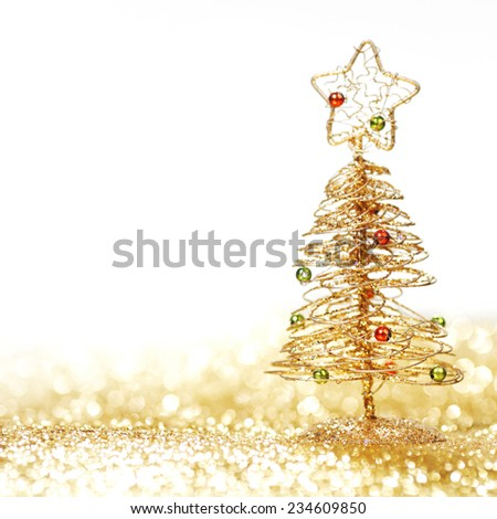 Toy golden decorative Christmas tree on glitter background