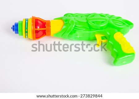 toy gun with spinning top on white paper background - stock photo