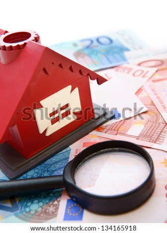 Toy house  and magnifier on the money. - stock photo