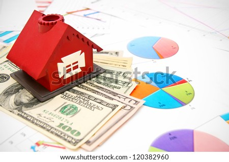 Toy house and money on the graphs. - stock photo