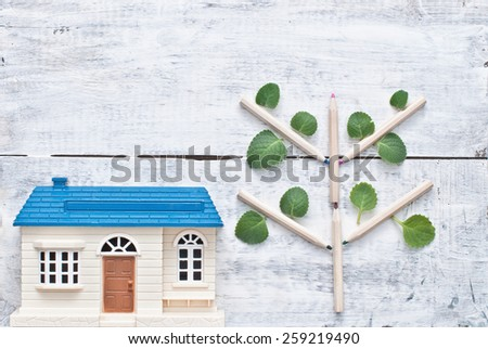 Toy house and pencil tree with green leaves on wooden background - stock photo