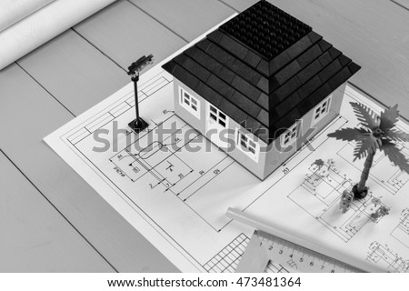 Toy house (constructor) on table with the drawings and business accessories