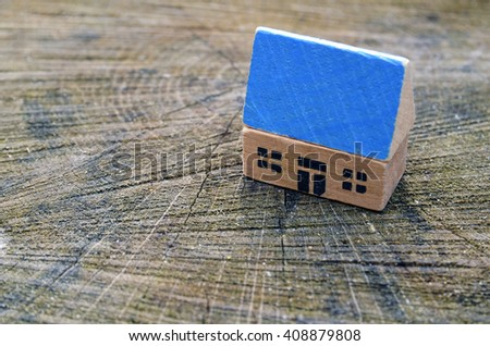 Toy house made of wood on wooden texture. The construction of buildings from natural materials.The concept of eco-estate. Eco-friendly housing. - stock photo