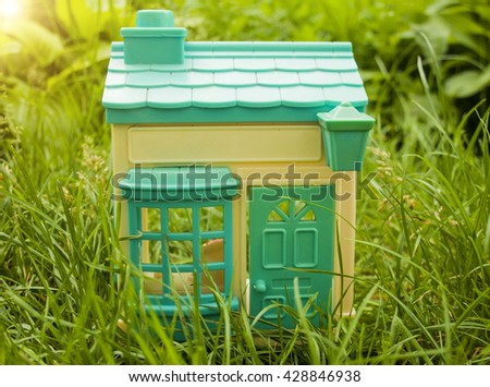 Toy house on a background of green grass - stock photo