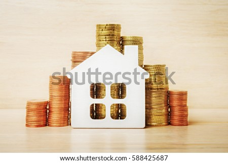 Toy house with Euro coins, mortgage and saving concept