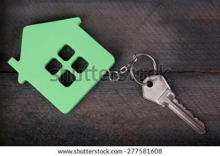 Toy house with key on wooden background - stock photo