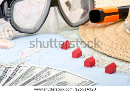 Toy houses on a map with euro banknotes, snorkel mask and seashells