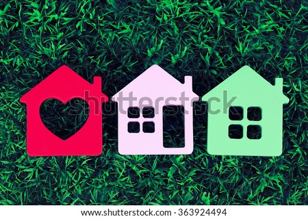 Toy houses on grass background, close-up - stock photo