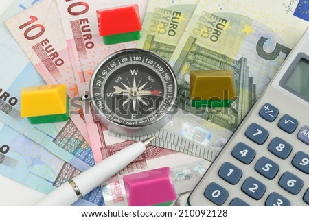 Toy houses surrounding a compass on Euro cash, a property finance metaphor. - stock photo