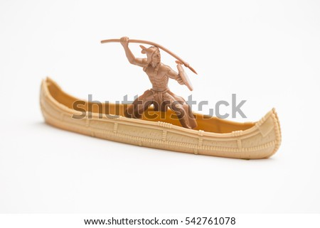 Toy indian with spear in a canoe