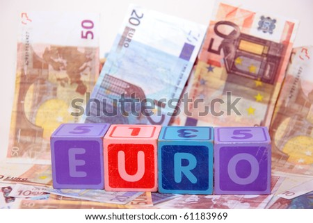 toy letters that spell euro against a cash background