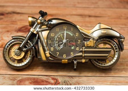 toy motorcycle clock on a table close-up - stock photo