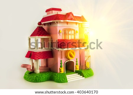 Toy pink two-storey cottage with a lawn near the house at sunset. - stock photo