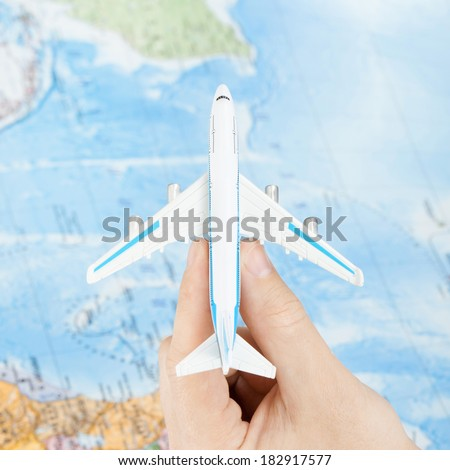 Toy plane in hand with world map on background - view from top - 1 to 1 ratio