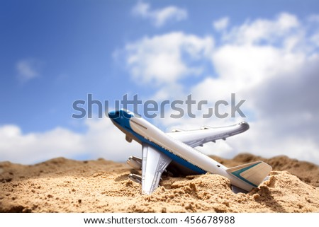 toy plane rises from the sand beach against the blue sky with clouds, concept for holidays and airline travel, copy space, selected focus, very narrow depth of field - stock photo