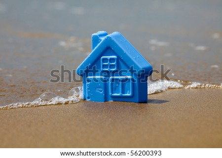 Toy plastic house on the sand washes wave - stock photo