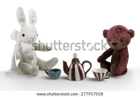 toy rabbit and bear are  sitting near teapot and cup - stock photo