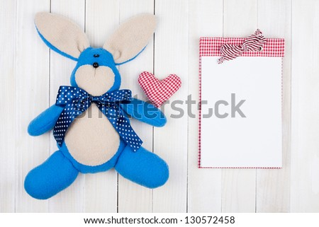 Toy rabbit, heart and notepad on white wood background - stock photo