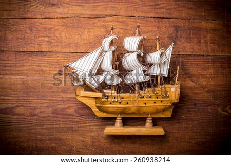 Toy sailboat on a wooden background with copy space - stock photo