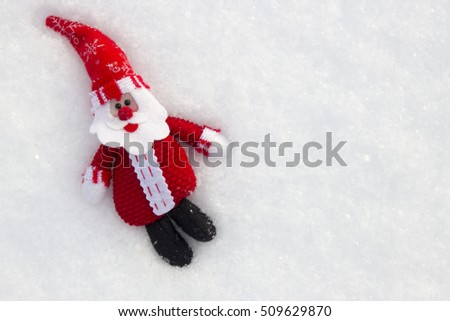 Toy Santa Claus on the snow in the New Year and Christmas