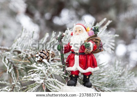 Toy Santa Claus standing on the fir tree branch. - stock photo